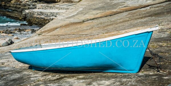 Turquoise Fishing Boat on the rocks